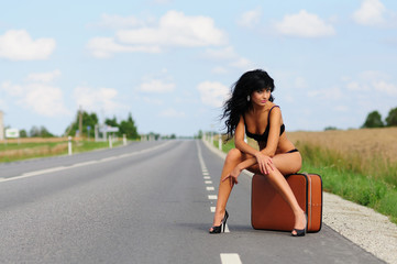 brunette with suitcase in road, highway.