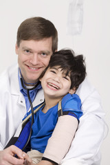 Male doctor holding five year old disabled patient