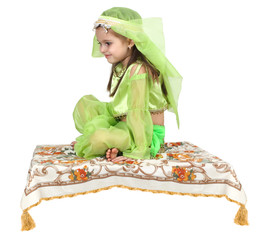 little arabian girl sitting on a flying carpet
