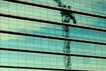 Riflesso di una gru sulla parete a specchio di un edificio