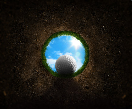 Golf ball falling into the cup