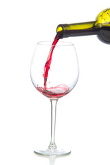 Red wine splash being poured into a wine glass