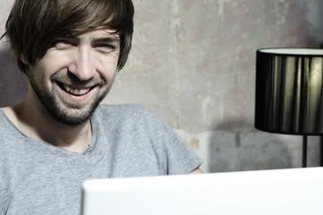 Lachender Junger mann hinter laptop