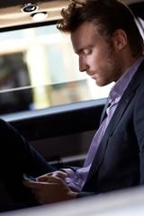 Smart man texting on cellphone in elegant car