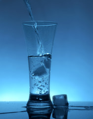 Water flows into the glass with ice