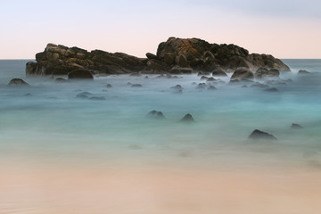 Rocks in the ocean on the horizon after sunset