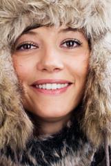 Attraktiv lächelnde junge Frau mit Pelzmütze