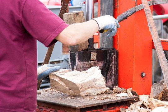 worker splitting logs with power splitter