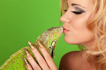 Portrait of a young woman with beautiful manicure kissing a igua