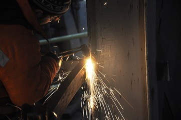 Worker from top, cutting steel in flares, focus in work