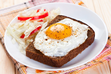Fried egg on slice bread.