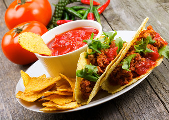 plate with taco, nachos chips, tomato dip