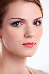 Closeup portrait of beautiful young woman over white