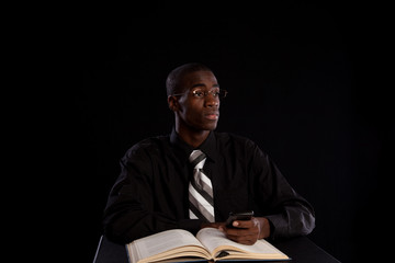 Handsome black man studying from a book and thinking