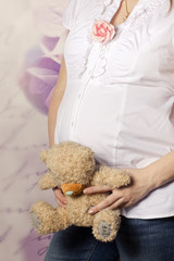 Pregnant woman holding a teddy bear over her belly