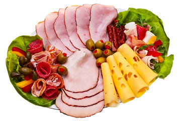 Dish with sliced smoked ham, salami rolls and cheese.