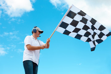 Man waving a checkered flag on a raceway