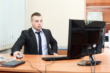 Portrait of smart young businessman working on pc at office