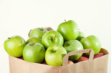 Shopping paper bag full of green apples isolated over white
