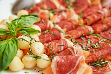 Tapas with cured ham, basil and melon balls