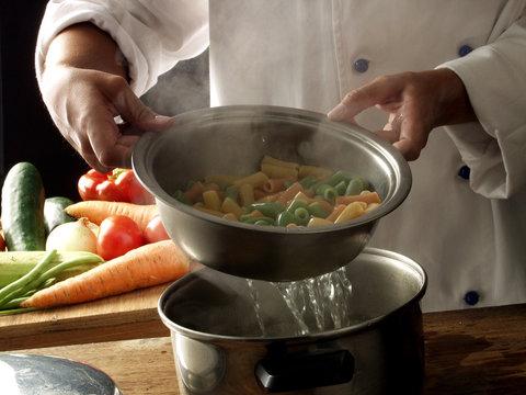 escurriendo y cocinando verduras hervidas.