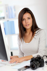 Young woman photo reporter sitting in front of desktop computer