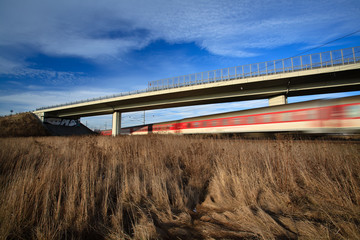 Fast train passing under a bridge on a lovely summer day
