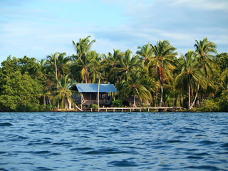 Rustic Amerindian hut with dock on tropical shore with coconut trees, Bocas del Toro, Panama, Central America