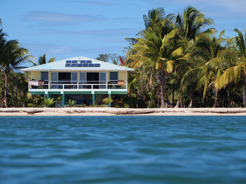Beach house with solar panels on a tropical beach seen from water surface, Caribbean sea