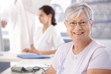 Senior woman smiling at doctor's room