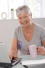 Happy elderly woman with laptop