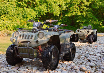 ATV's parked on the shore of a mountain river.