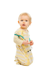 Confused baby with stethoscope sitting on floor