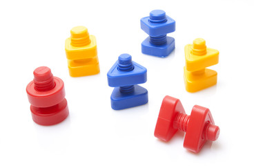 Colourful toy nuts and bolts on white background