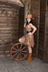 CowGirl with a ancient cart wheel standing in old depot