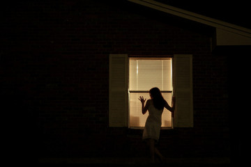 Woman at Window at Night