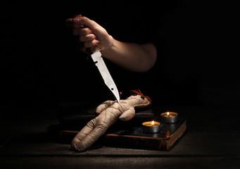 Voodoo doll girl pierced by knife
