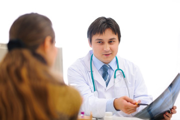 Smiling medical doctor showing roentgen to patient