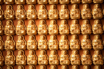 Little golden buddha on the wall background .