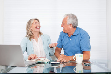 Couple At Dining Table Working on Laptop