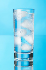 Glass of ice water on blue background
