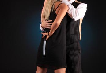 Frau beim Küssen versteckt Messer hinter dem Rücken