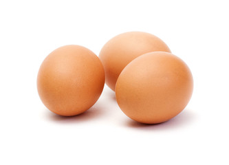 Three brown eggs on white background