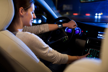 Driving a car at night -  young woman driving her modern car