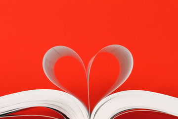 book with pages in heart shape over red background