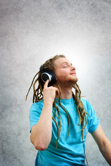 Young Man with Dreadlocks Listening to Music on Headphones