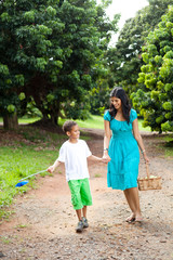 happy mother and son walking in fruit orchard