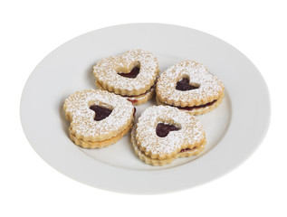 White plate with four heart shaped cookies