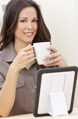 Woman Using Tablet Computer At Home Drinking Tea or Coffee