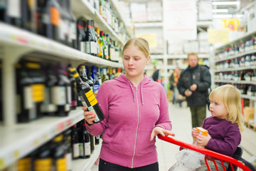 mother and daughter in vine section in supermarket